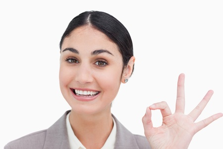 Close up of smiling businesswoman giving her approval against a white background photo