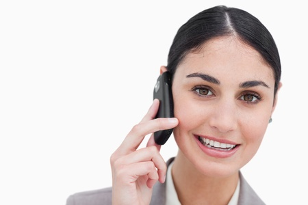 Close up of smiling businesswoman talking on cellphone against a white background photo