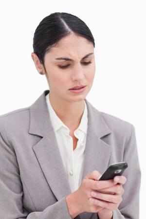 Close up of businesswoman confused by text message against a white background photo