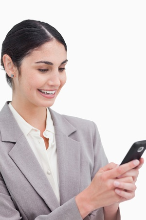 Close up of smiling businesswoman reading text message against a white background photo