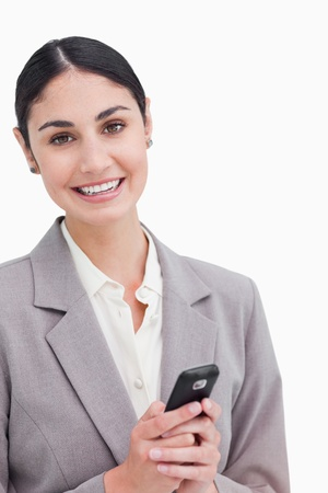 Close up of smiling businesswoman holding cellphone against a white background photo