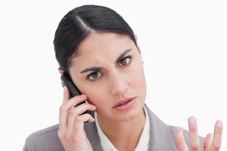 Close up of angry businesswoman on her cellphone against a white background photo