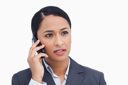 caller: Close up of saleswoman listening to caller against a white background