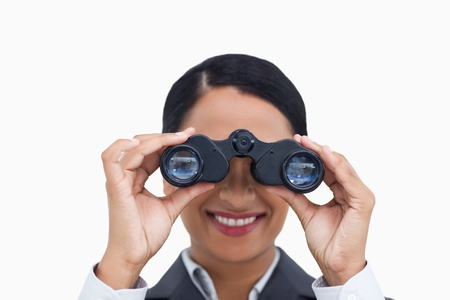 Close up of smiling saleswoman using spy glasses against a white background photo