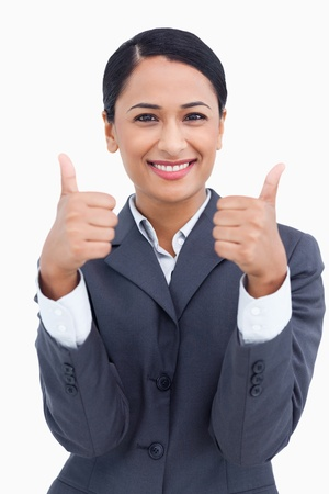 Close up of smiling saleswoman giving thumbs up against a white background Stock Photo - 13675286