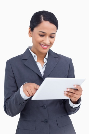 Close up of smiling saleswoman using her tablet computer against a white background photo