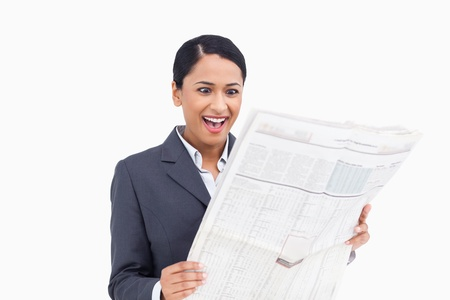 Close up of surprised saleswoman reading the news paper against a white background photo