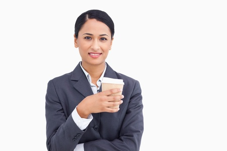Close up of smiling saleswoman with paper cup against a white background photo