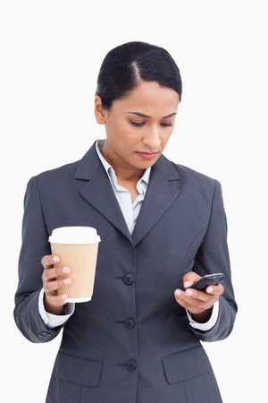 Close up of saleswoman with paper cup writing text message against a white background photo