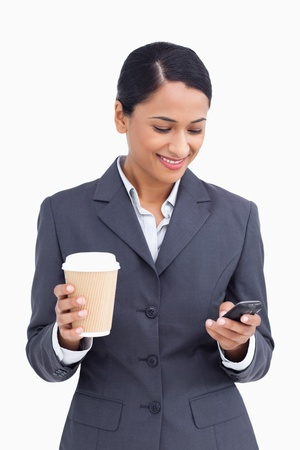 Close up of saleswoman with paper cup reading text message against a white background photo