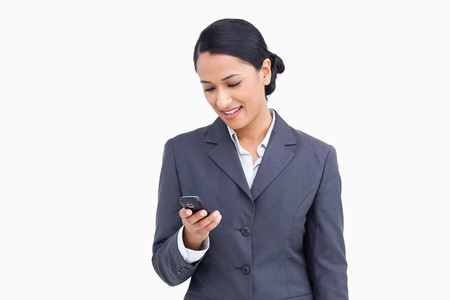 Close up of smiling saleswoman reading text message against a white background photo
