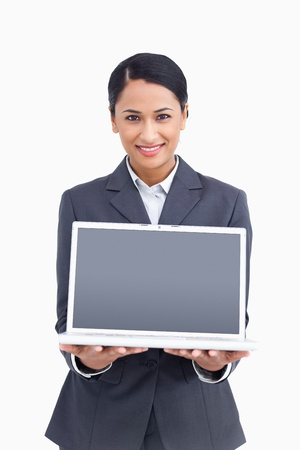 Close up of smiling saleswoman presenting screen of laptop against a white background photo