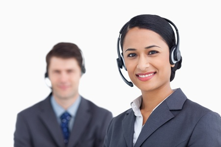Close up of smiling call center agents against a white background photo