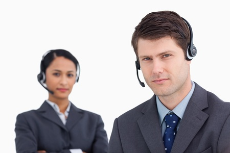 Close up of serious looking call center agents against a white background photo