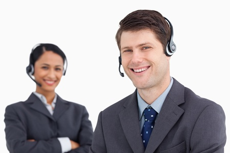 Close up of smiling male call center agent with colleague behind him against a white background photo