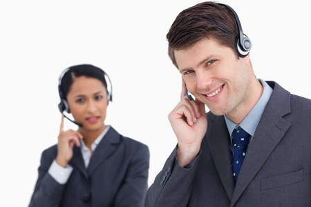 Close up of smiling call center agent with co-worker behind him against a white background photo