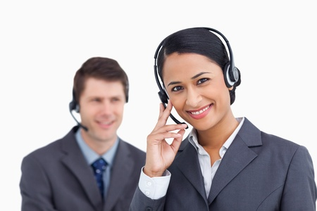 Close up of smiling call center agent with colleague behind her against a white background photo