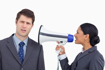 Close up of saleswoman with megaphone yelling at colleague against a white background photo