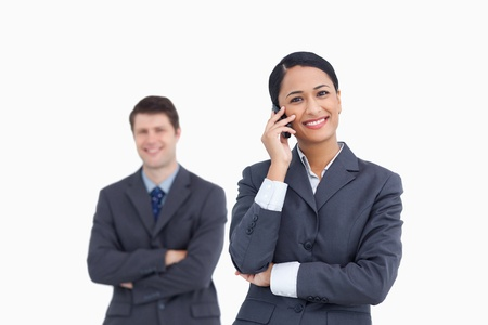 Close up of saleswoman on the phone with colleague behind her against a white background photo