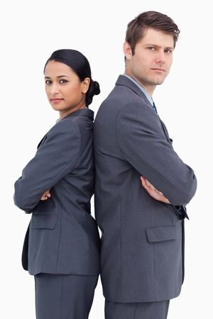 Close up of confident salesteam standing back to back against a white background photo