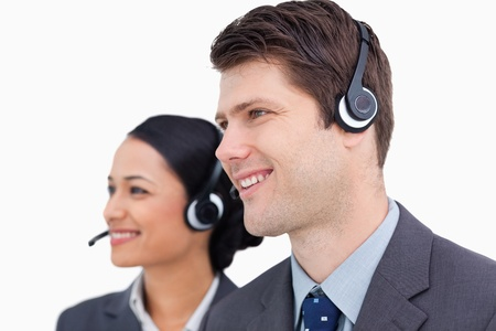 Close up of smiling call center team against a white background photo