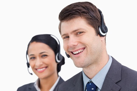 Close up of smiling call center employees against a white background photo