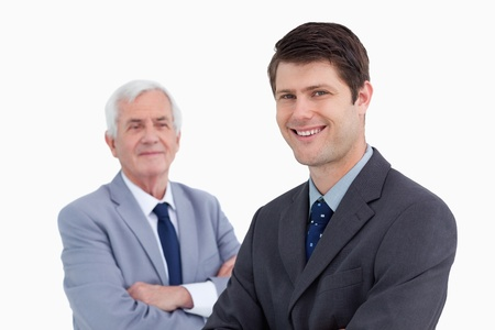 Close up of smiling businessman with his mentor behind him against a white background photo