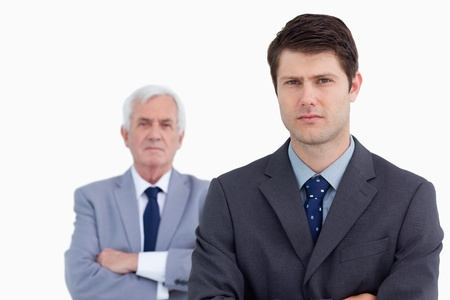Close up of serious businessman with his mentor behind him against a white background photo