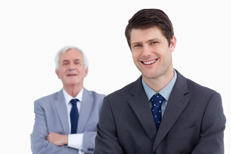 Close up of smiling businessman with his boss behind him against a white background photo