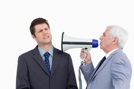 Close up of mature businessman with megaphone yelling at colleague against a white background photo