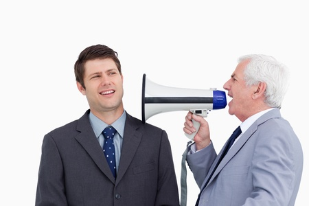Close up of mature businessman with megaphone yelling at employee against a white background photo