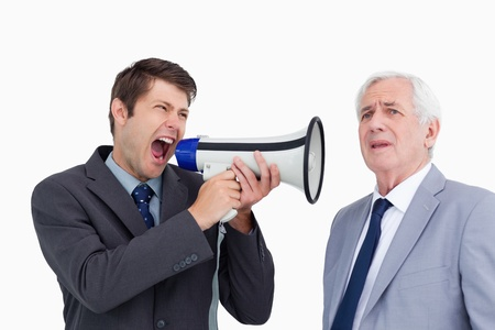 Close up of businessman with megaphone yelling at his boss against a white background photo