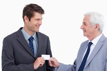 Close up of businessmen exchanging business card against a white background photo