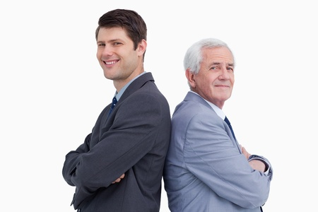 Close up of businessman and his mentor standing back to back against a white background photo