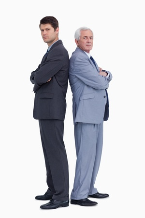 Businessmen standing back to back against a white background photo