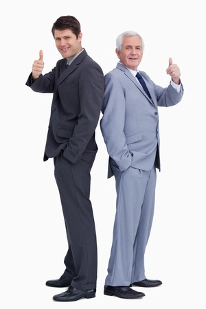 Businessmen standing back to back giving thumbs up against a white background photo