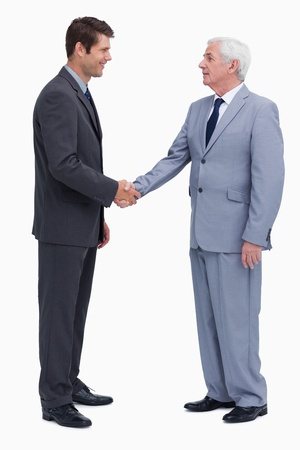 Young and mature businessmen shaking hands against a white background photo