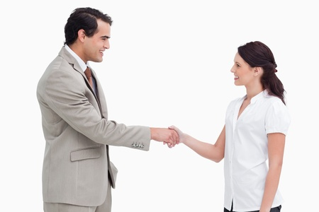 salespeople: Side view of salespeople shaking hands against a white background Stock Photo
