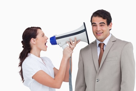 Saleswoman with megaphone yelling at colleague against a white background photo