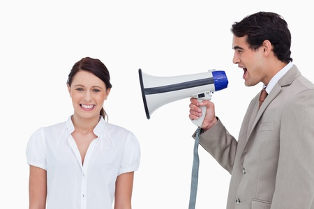 Salesman yelling at colleague with megaphone against a white background photo