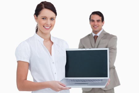 Smiling saleswoman presenting laptop screen with colleague behind her against a white background photo
