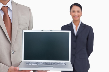 Laptop being presented by salesman with colleague behind him against a white background photo