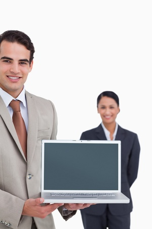 Laptop being presented by smiling salesman with colleague behind him against a white background photo