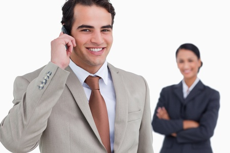 Salesman on his cellphone with colleague behind him against a white background Stock Photo - 13675255