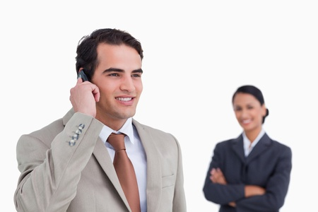 Smiling salesman on his mobile phone with colleague behind him against a white background photo