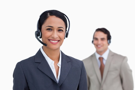 Smiling telephone support employee with colleague behind her against a white background photo