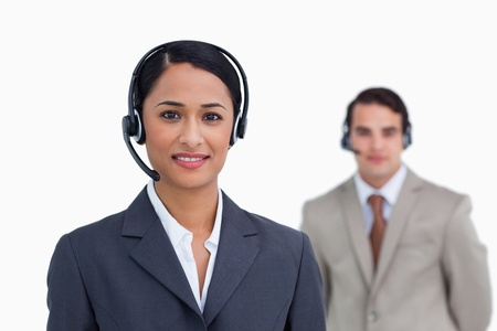 Smiling telephone support worker with colleague behind her against a white background photo