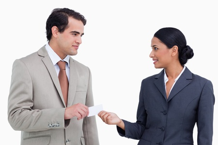 Saleswoman handing business card over to costumer against a white background photo