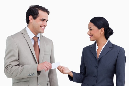 Smiling sales partner exchanging business cards against a white background photo