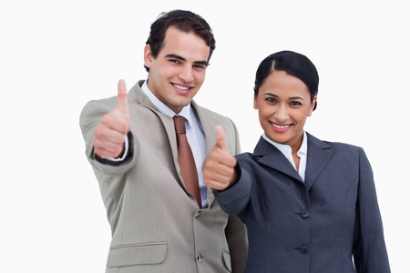 two thumbs up: Smiling salespeople giving thumbs up against a white background Stock Photo